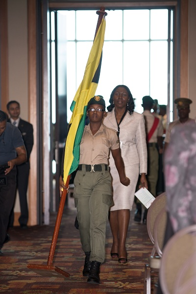 Ms. Carolyn Lewis, Director of Audit, Jamaica enters during the procession of  national flags.